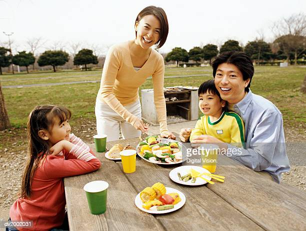 Family Sitting at a Picnic Table Enjoying a Meal