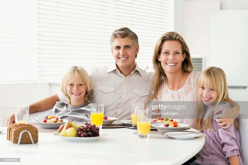 Family Sitting at Breakfast Table Smiling : Stock Photo