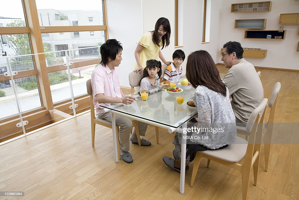 Family sitting at dining table : Stock Photo