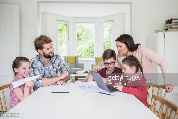 Familie sitzt am Tisch, Tochter Hausaufgaben auf Laptop, Mädchen spielen mit Papier Flugzeug