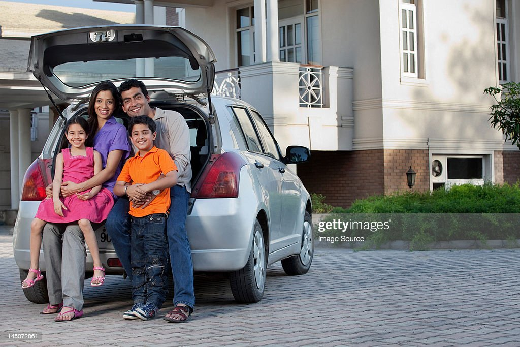 Family sitting at the back of a car : Stock Photo