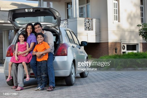 Family sitting at the back of a car : Stockfoto