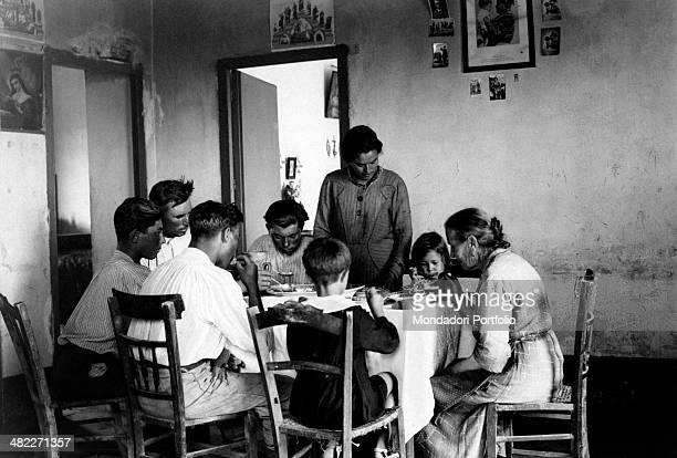 A family sitting at the table during the area regeneration sponsored by the Ente di Colonizzazione del Latifondo Siciliano Sicily 10th October 1942