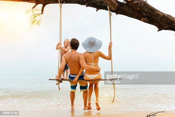 Family sitting at tropical swing