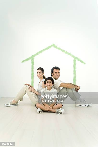 Family sitting back to back in front of outline of house painted on wall