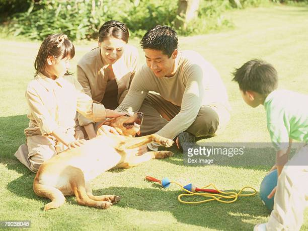 Family sitting in a park with pet dog