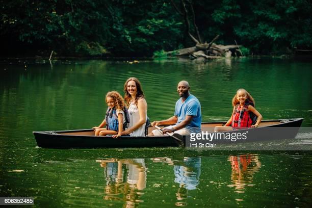 Family sitting in canoe in lake