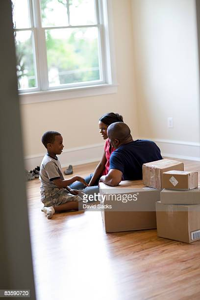 Family sitting in empty room with moving boxes