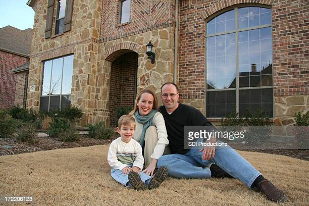 Family Sitting In Front Of Their New House Purchased