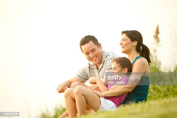 Family sitting in grass together