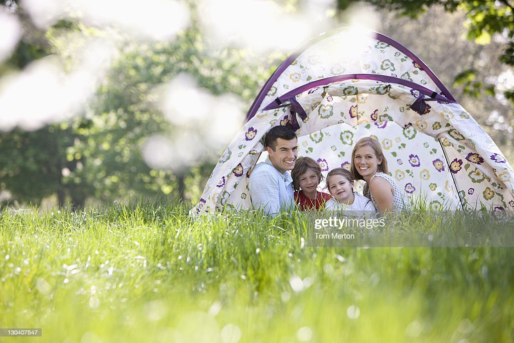 Family sitting in tent in park : Stock Photo