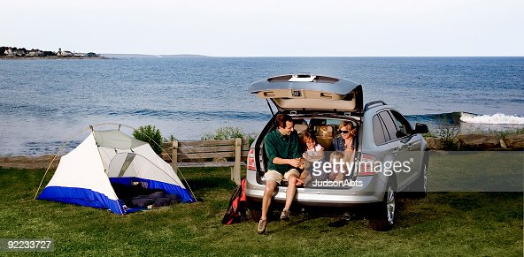 A family sitting in the back of an SUV outdoors