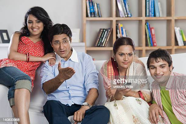 Family sitting on a couch watching TV together