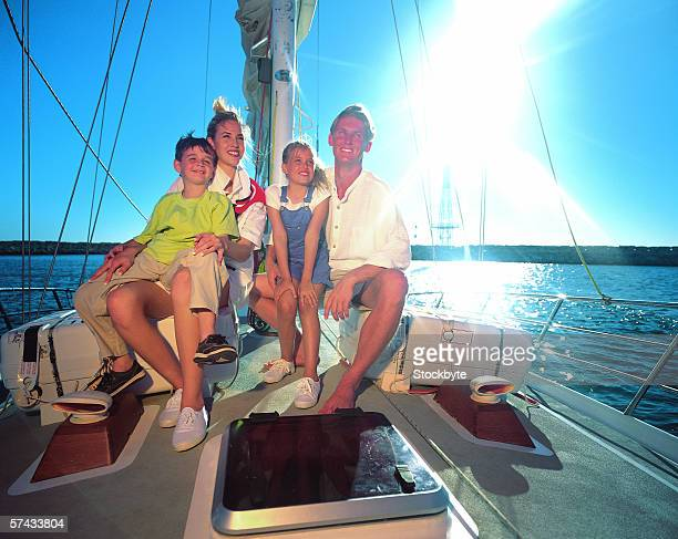 family sitting on a yacht smiling