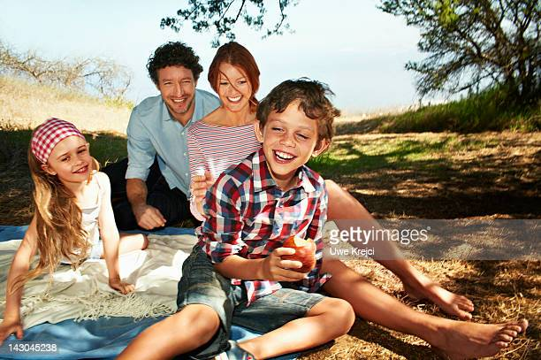 Family sitting on blanket, outdoors, smiling