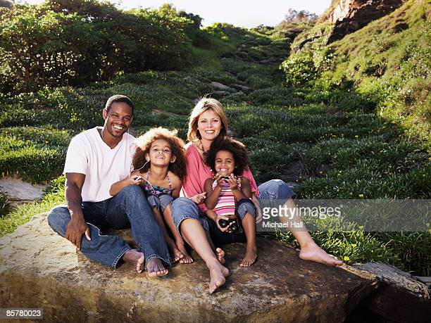 Family sitting on boulder