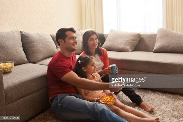 Family sitting on carpet watching television