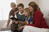 Family sitting on couch and reading Holy Bible