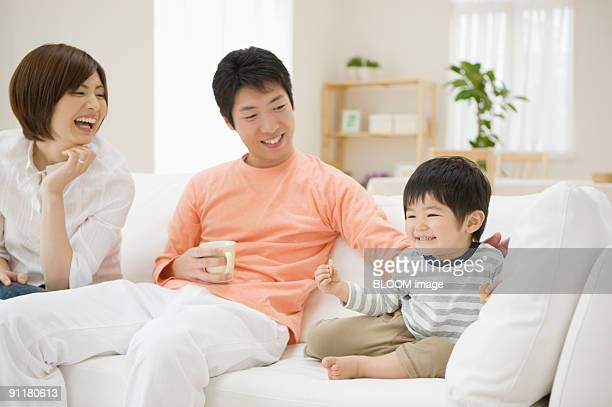 Family sitting on couch, smiling