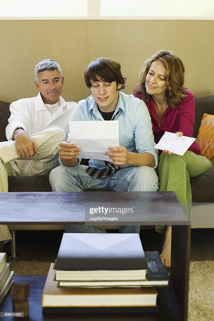 Family sitting on couch together reading a letter : Stock Photo