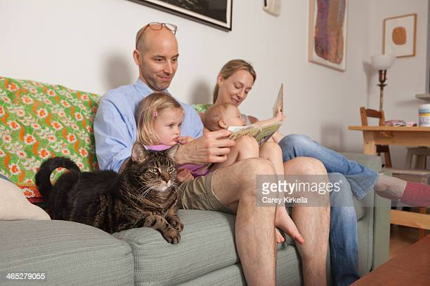 Family sitting on couch with their cat