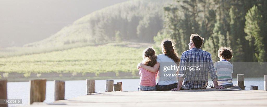 Famille assis sur le quai près du lac : Photo