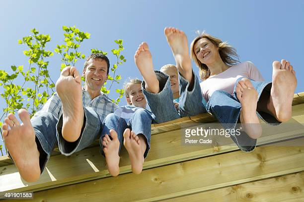 Family sitting on edge of decking, view from below