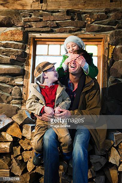 Family sitting on logs in rustic house