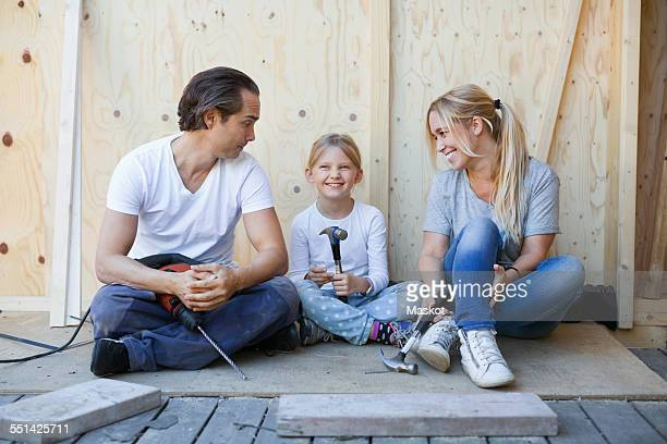 Family sitting on porch of house being renovated