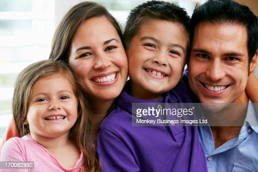Family Sitting On Sofa At Home Together : Stock Photo