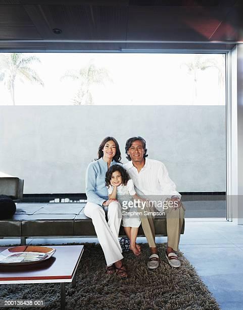 Family sitting on sofa in living room, portrait