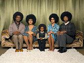 Family sitting on sofa, smiling, portrait
