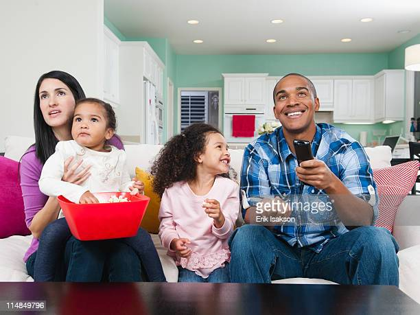 Family sitting on sofa watching television