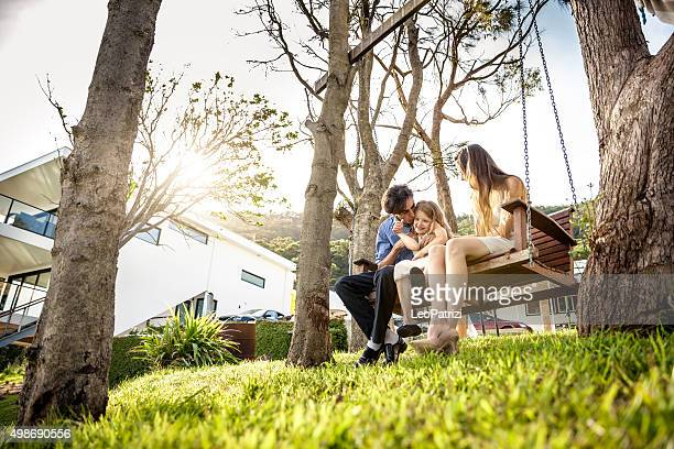 Family sitting on the backyard of their house in Australia