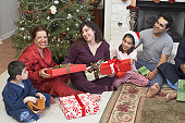 Family sitting on the floor with Christmas gifts