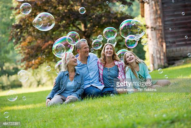 A family sitting on the grass outside a bar,blowing bubbles and laughing.