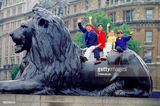 Family sitting on the Lion Sculpture in Trafalgar Square and waving at the viewer; London, England.