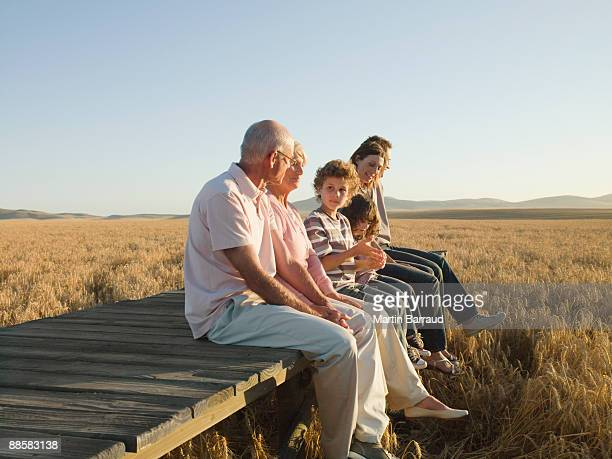 Family sitting on wooden dock in remote wheat field