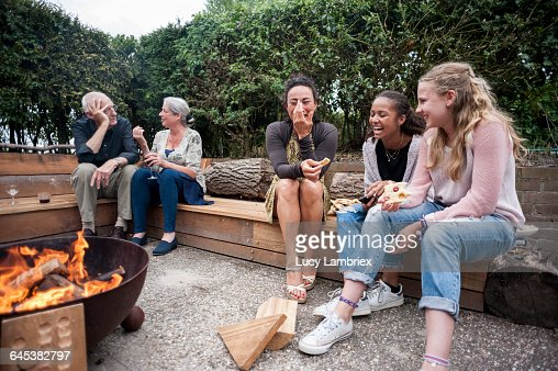 Family sitting outdoors by a fire : Stockfoto