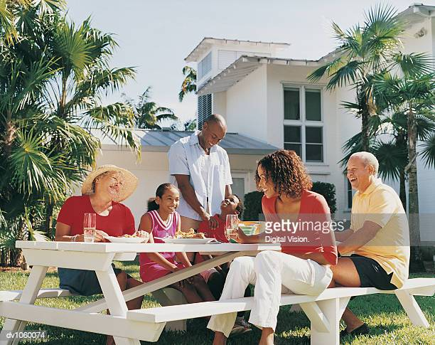 Family Sitting Outdoors Enjoying a Meal