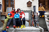 Family sitting outside barn with skis