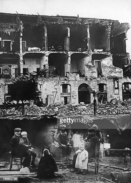 A family sitting round a fire in the aftermath of the earthquake which destroyed the city of Messina on the island of Sicily on 28th December 1908...