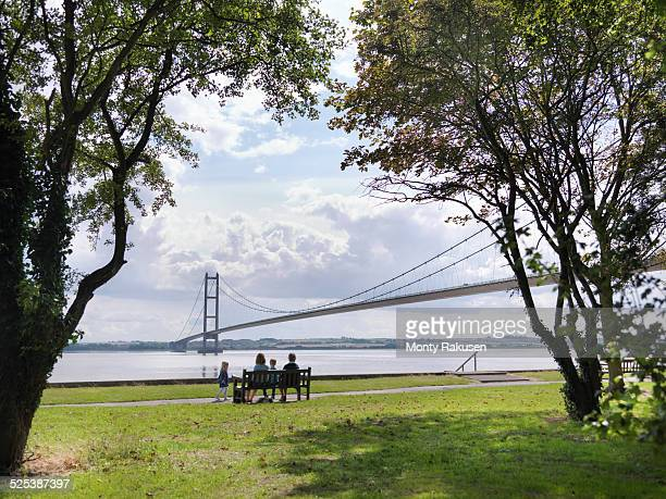 Family sitting together on bench looking at suspension bridge. The Humber Bridge, UK was built in 1981 and at the time was the worlds largest single-span suspension bridge