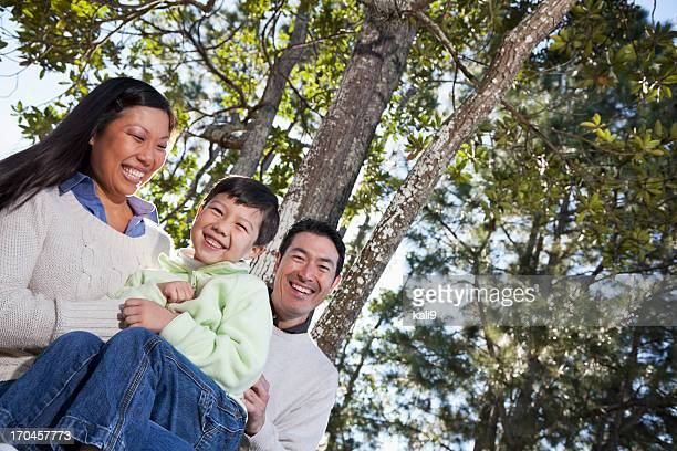 Family sitting under trees