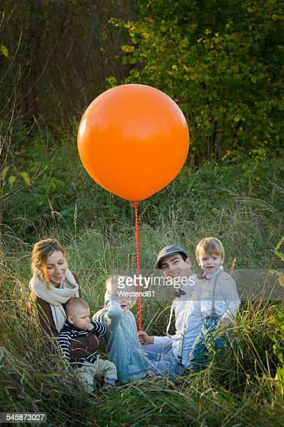 Family sitting with balloon on meadow
