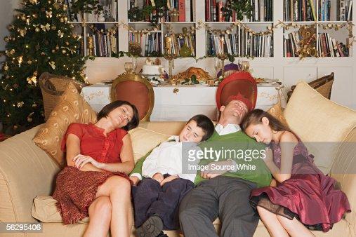 Family sleeping on sofa at Christmas : Stock-Foto