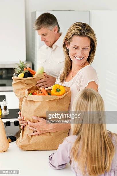 Family Smiling and Putting Away Groceries