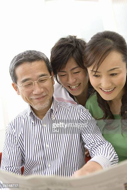 A Family Smiling and Reading a Newspaper Together, Front View