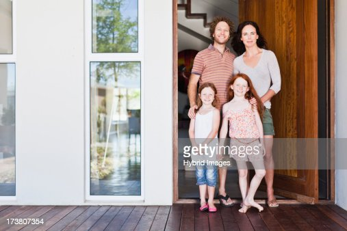 Family smiling at front door : Stock Photo