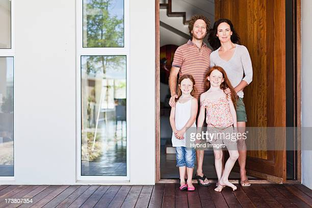 Family smiling at front door